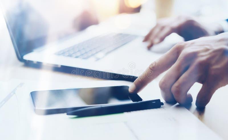 Opinión del primer el hombre que trabaja en el teléfono móvil moderno en la oficina y que señala el finger al botón casero en sma imagen de archivo