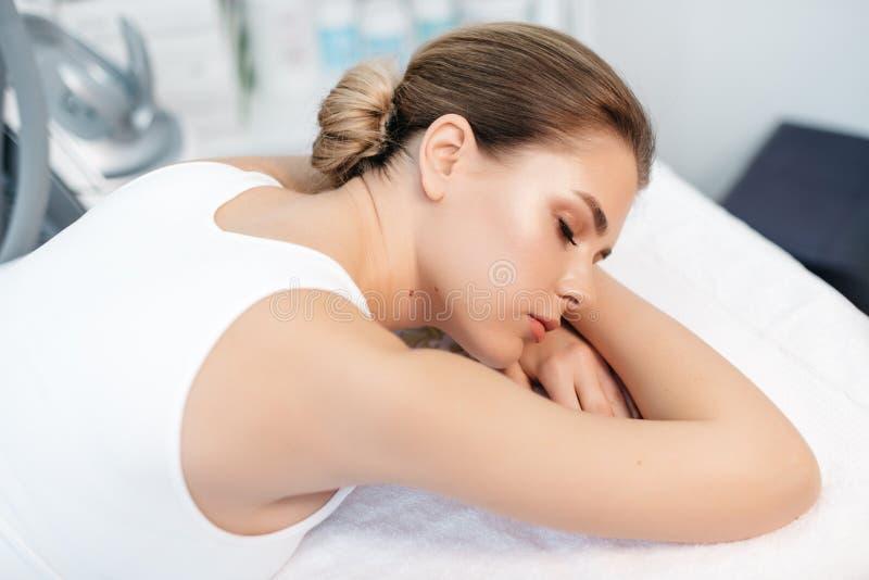 Opinión del primer la mujer pacífica joven hermosa con el maquillaje natural que espera el masaje mientras que miente en el balne imagen de archivo libre de regalías