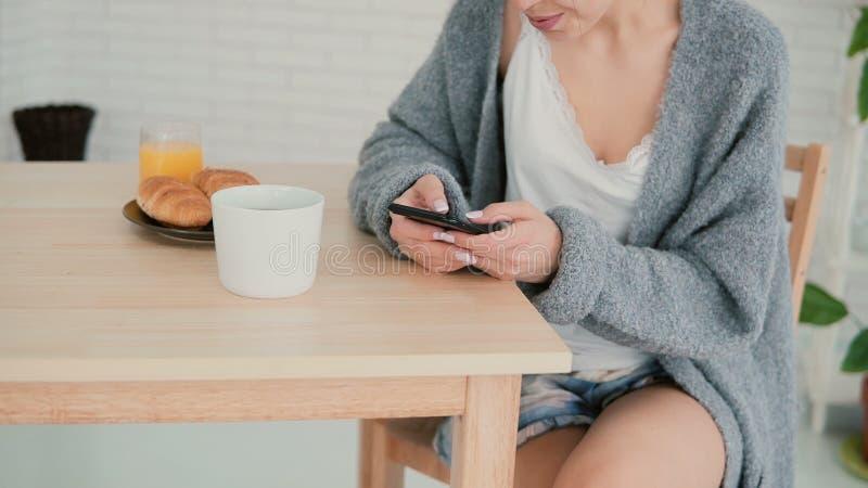 Opinión del primer la mujer que tiene el desayuno y Internet de la ojeada, usando pantalla táctil La muchacha lee nuevo en smartp imagen de archivo