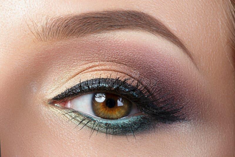 Opinión del primer del ojo de la mujer con maquillaje de la tarde fotos de archivo