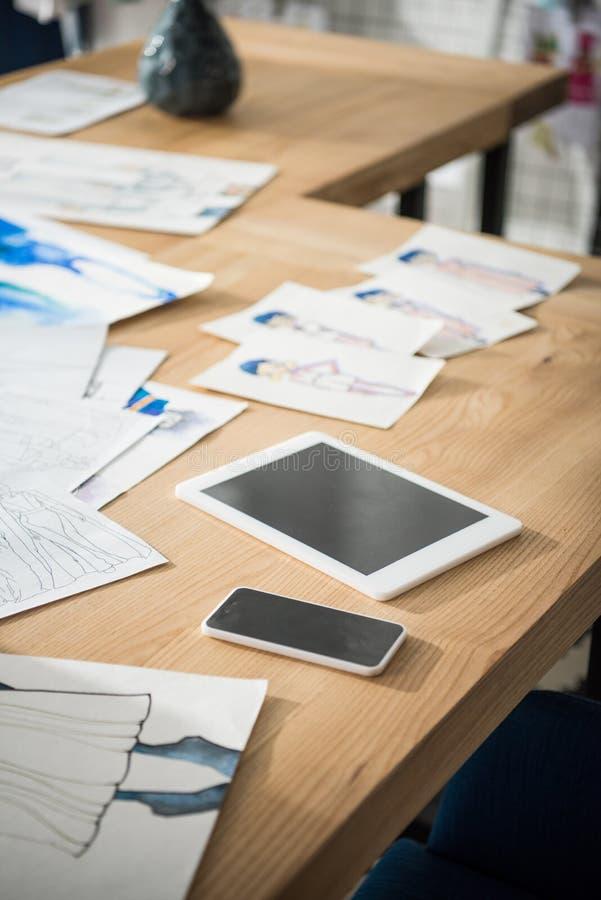 opinión del primer del smartphone y de la tableta digital con las pantallas en blanco y los bosquejos de la moda foto de archivo