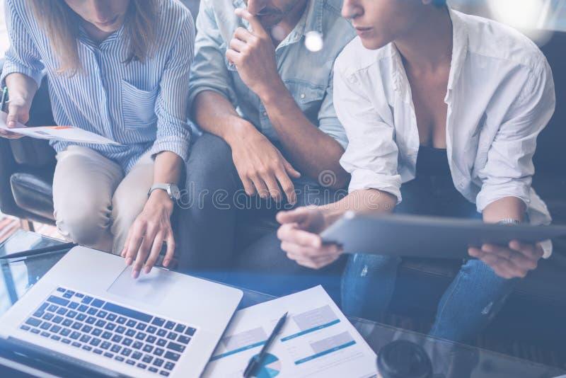 Opinión del primer tres compañeros de trabajo jovenes que trabajan en el ordenador portátil móvil en la oficina Tableta de la ten imágenes de archivo libres de regalías