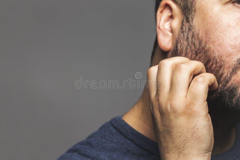 Opinión del primer un hombre que rasguña la barba, gesto pensativo foto de archivo