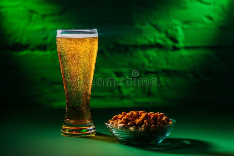 opinión del primer del vidrio con la cerveza fría fresca y los cacahuetes salados imagenes de archivo