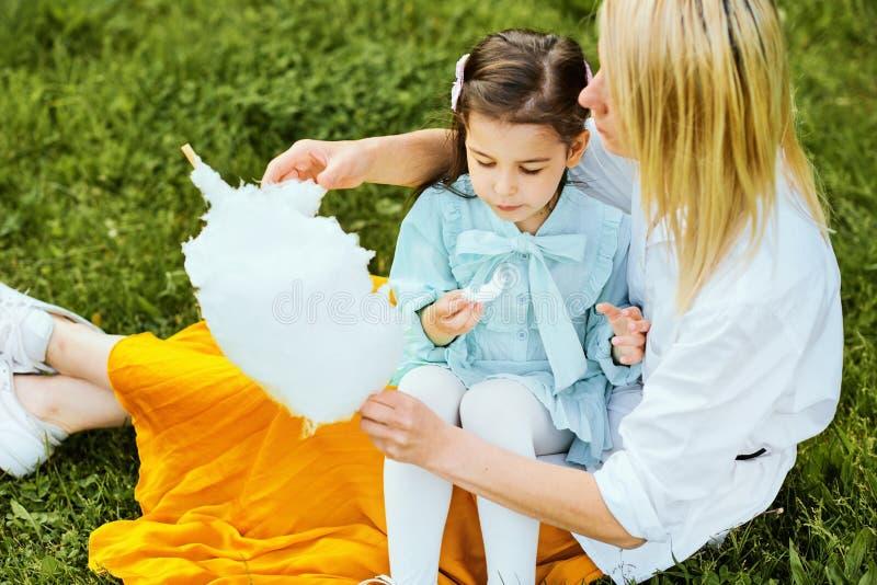 Opinión desde arriba de la hija hermosa que come el caramelo de algodón con su madre joven en el parque que se sienta en la hierb imágenes de archivo libres de regalías
