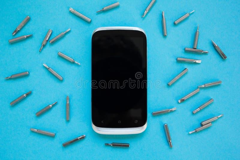 Opinión desde arriba sobre smartphone con las herramientas en un fondo azul fotos de archivo