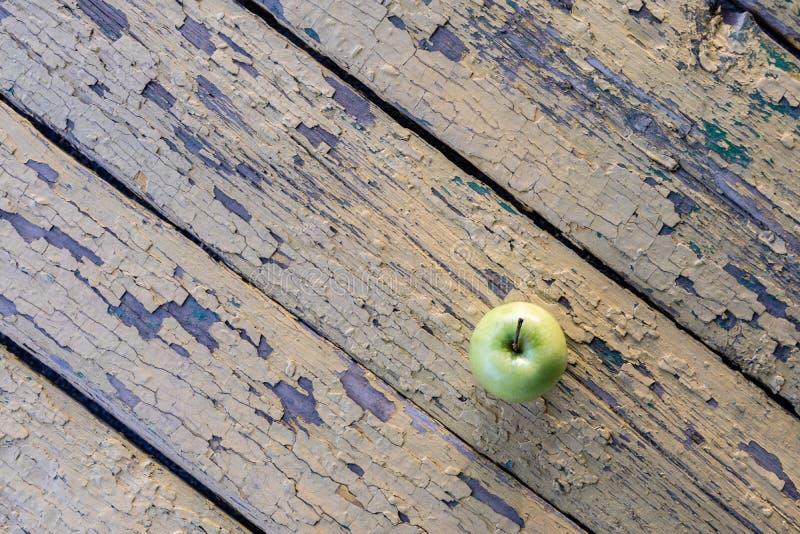 Opinión desde arriba sobre una manzana verde situada en un fondo de viejos tableros con la peladura de la pintura amarilla imagen de archivo libre de regalías