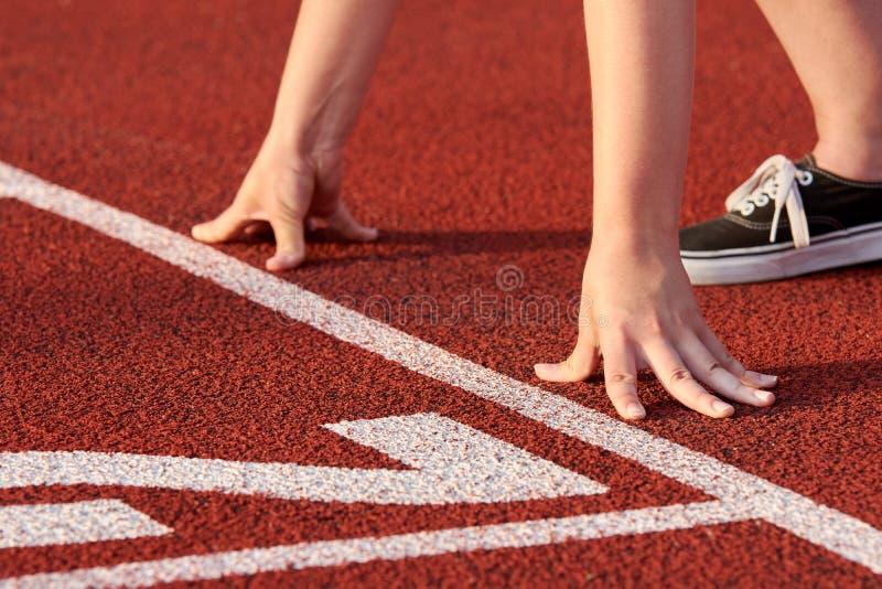 Opinión el atleta de sexo femenino en el comienzo de la raza Se coloca en una pista roja del tartán y está listo para ayunar func imagen de archivo libre de regalías