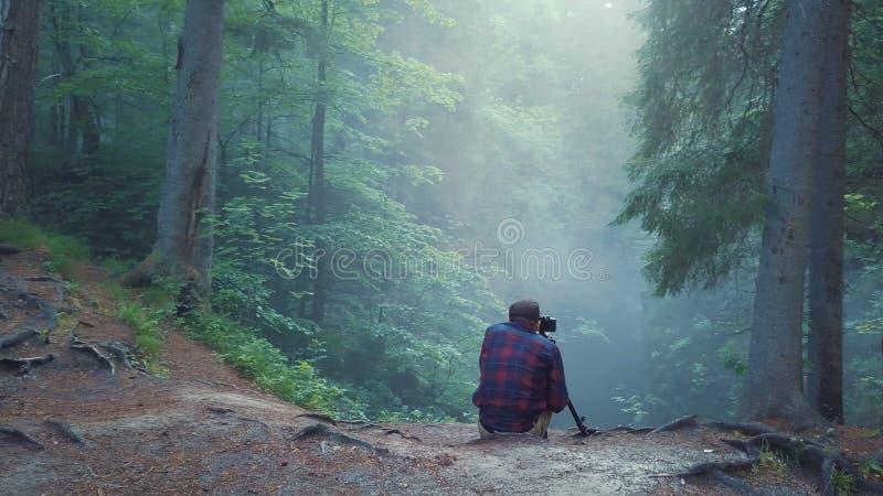 Opinión el hombre en la camisa y los pantalones de tela escocesa que se sientan al borde del barranco profundo y que toman una im imágenes de archivo libres de regalías