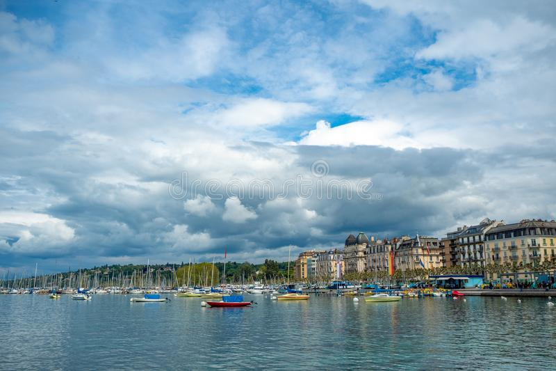 Opinión encantadora del panorama de los barcos que flotan en edificios del lago geneva en fondo del cielo azul de las nubes fotos de archivo libres de regalías