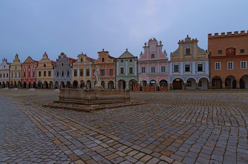 Opinión escénica de la mañana de la plaza principal en Telc medieval Fuente con la estatua de St Margaret y de los edificios colo imágenes de archivo libres de regalías