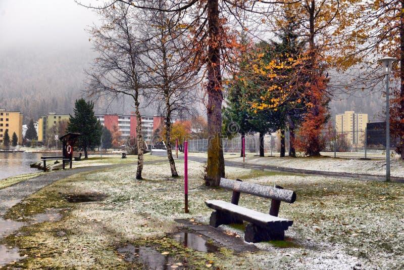 Opinión escénica del otoño con la primera nieve en un camino mojado de la suciedad en las montañas, los árboles y bosque en la ni imagen de archivo libre de regalías