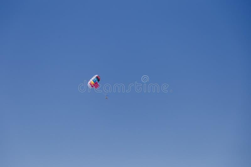 Opinión escénica espectacular sobre el mar y el cielo azul con la gente que vuela en un paracaídas colorido remolcado por un barc imagen de archivo