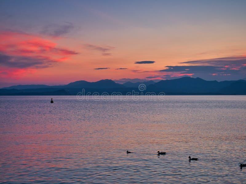 Opinión espectacular de la puesta del sol del pueblo de Bardolino en las orillas del lago Garda foto de archivo