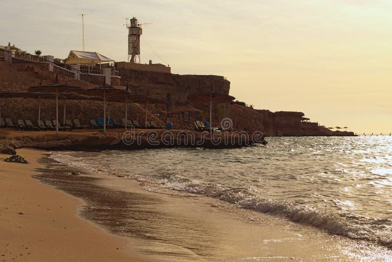Opinión fabulosa del paisaje de la playa hermosa con los paraguas y las camas de la playa, casa ligera en el top de la colina imagen de archivo