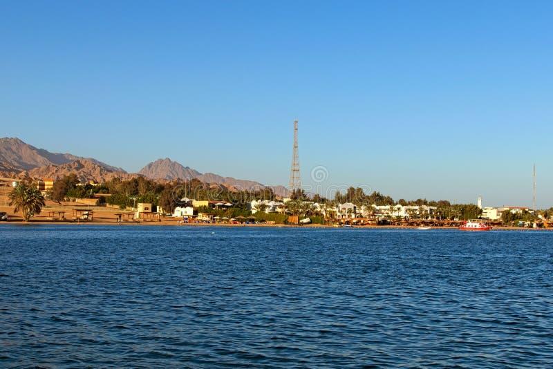 Opinión hermosa de la orilla de Mar Rojo, playa con algunos edificios, arena del paisaje Altas montañas en el fondo fotografía de archivo libre de regalías