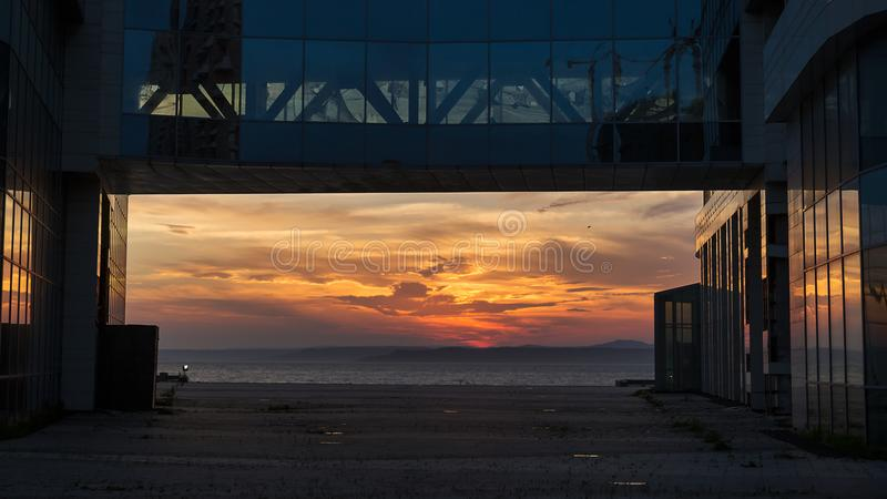 Opinión hermosa de la puesta del sol sobre el mar enmarcado por el edificio de oficinas de cristal foto de archivo