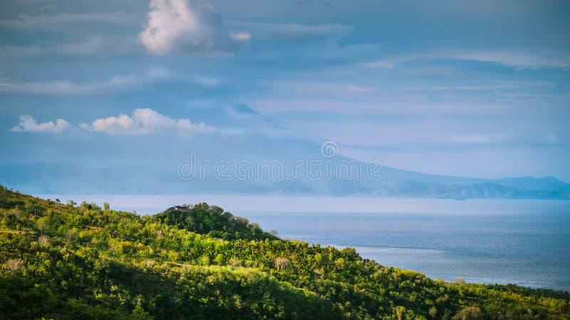 Opinión hermosa de la tarde a St Agung Vulcano en Bali de la isla de Nusa Penida Cubierto en parte por las nubes indonesia foto de archivo