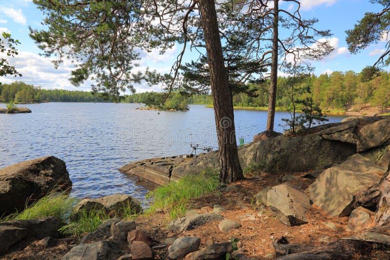 Opinión hermosa del paisaje de la naturaleza Lago con la línea rocosa de la costa, la superficie del agua azul y los árboles verd imagenes de archivo