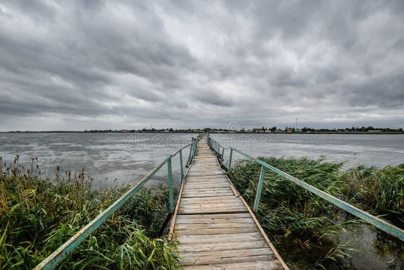 Opinión hermosa del verano del mar Báltico, de la playa arenosa, del rastro de tablones de madera y del cielo azul brillante, esc foto de archivo