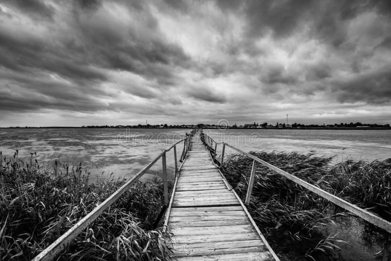 Opinión hermosa del verano sobre el lago hermoso, el puente de madera largo y el cielo dramático Lago sereno y un puente sin la g fotos de archivo