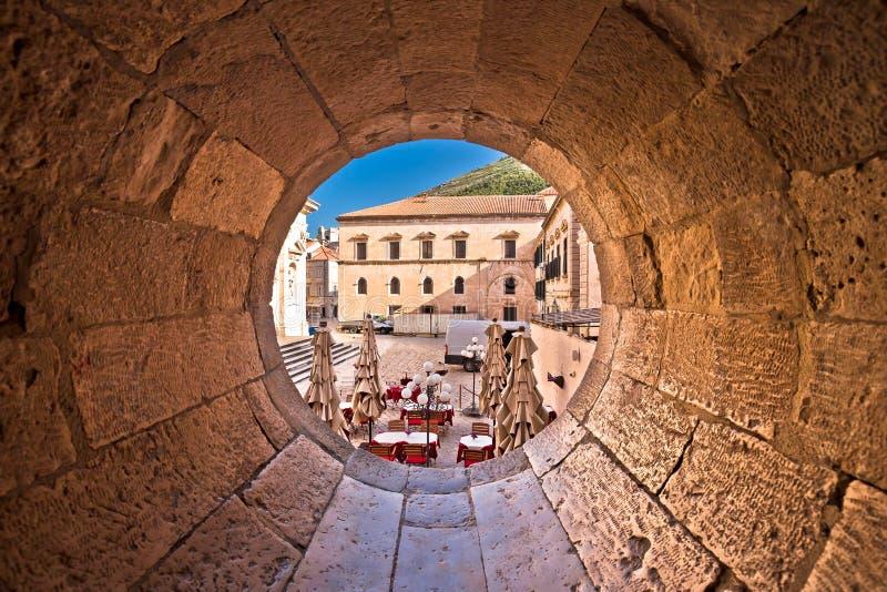 Opinión histórica de la calle de Dubrovnik a través de la ventana tallada de piedra fotos de archivo libres de regalías
