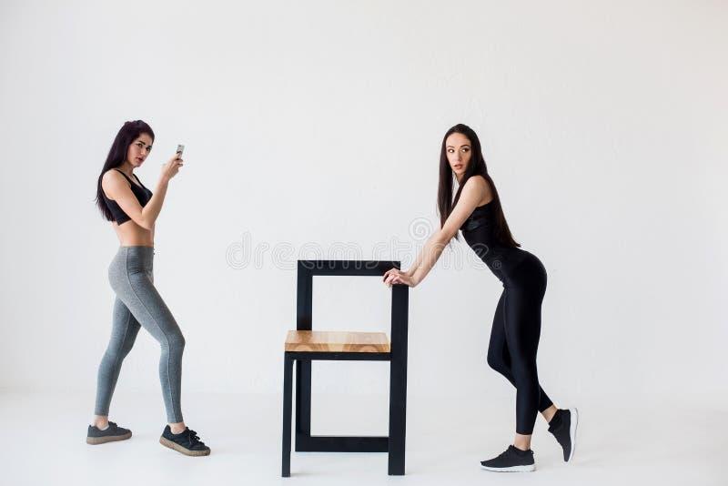 Opinión integral dos mujeres atléticas encantadoras de la aptitud Uno de ellos está tomando la foto de su amigo que se inclina en imágenes de archivo libres de regalías