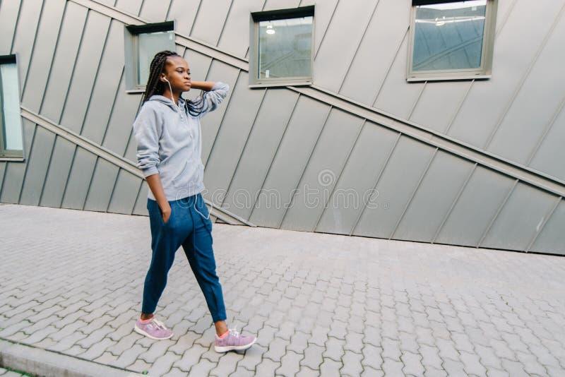 Opinión integral la muchacha africana confiada joven en ropa de deportes que camina a lo largo de la calle y que disfruta de músi fotografía de archivo libre de regalías