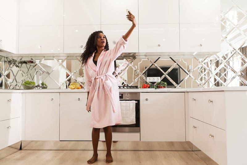 Opinión integral la mujer africana flaca hermosa en la albornoz rosada que toma el selfie en cocina elegante imagenes de archivo