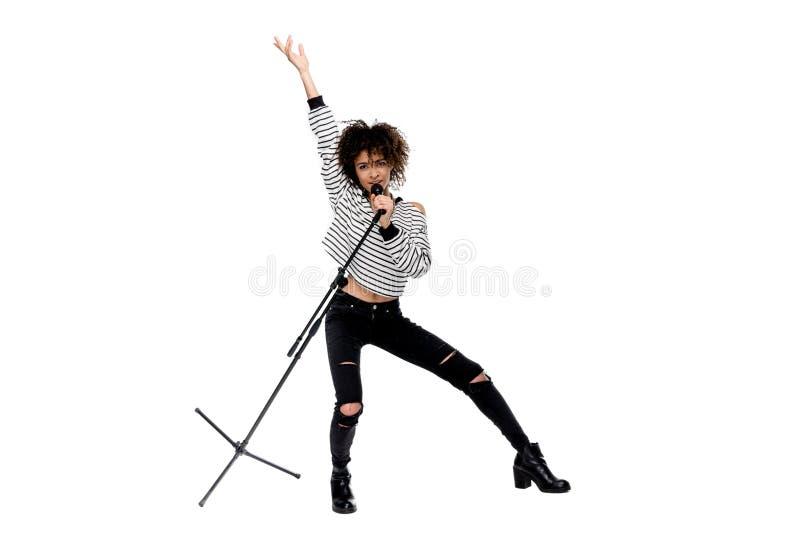Opinión integral la mujer joven hermosa con el micrófono que canta y que gesticula aislada en blanco fotografía de archivo