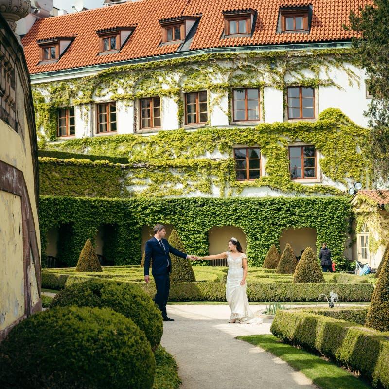 Opinión integral los recienes casados alegres que llevan a cabo las manos mientras que pasa su tiempo en el jardín viejo en Praga foto de archivo libre de regalías