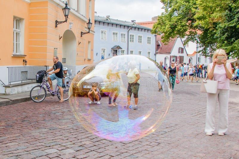 Opinión la vieja plaza de Tallinn y turistas a través de la burbuja de jabón grande fotos de archivo