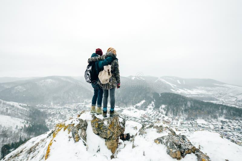 Opinión los amigos felices que abrazan mientras que camina en un aire libre nevoso del parque o del bosque fotos de archivo libres de regalías