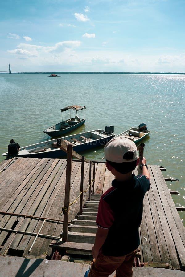 Opinión los niños que miran un lazo del hombre una cuerda para asegurar su barco a un embarcadero de madera imagenes de archivo