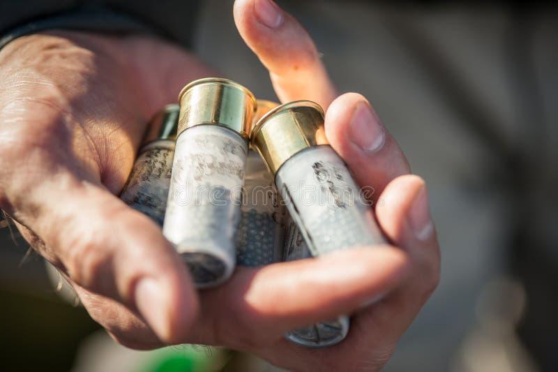 Opinión macra del primer de las manos del soldado que detienen a patrón de las balas de la escopeta foto de archivo