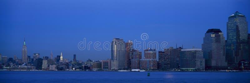 Opinión panorámica de la noche del horizonte del Empire State Building y del Lower Manhattan, NY donde las torres del comercio mu imagen de archivo libre de regalías