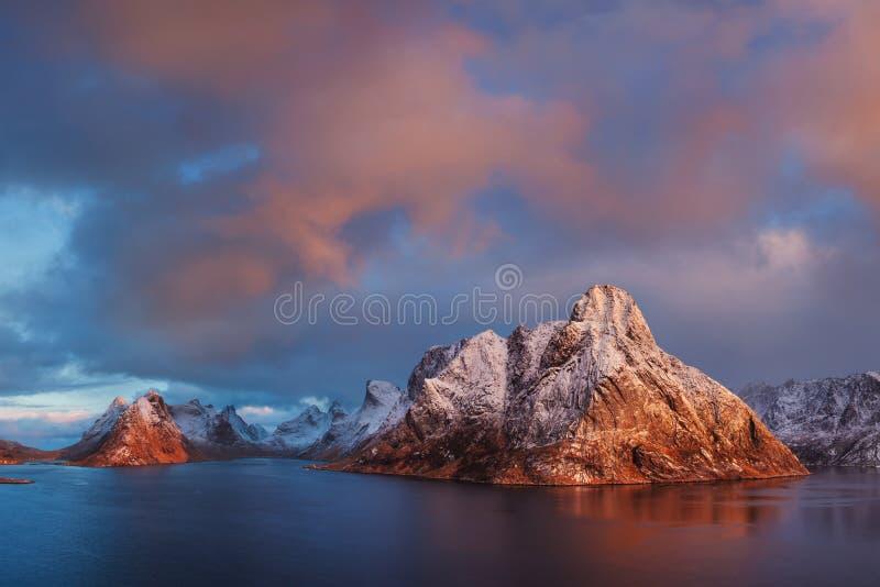 Opinión panorámica de la puesta del sol o de la salida del sol sobre las montañas imponentes en las islas de Lofoten, Noruega, pa fotos de archivo