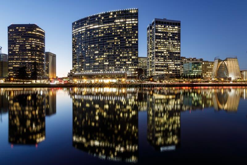 Opinión panorámica del horizonte de Oakland con el lago Merritt Reflections en las horas azules imagen de archivo libre de regalías