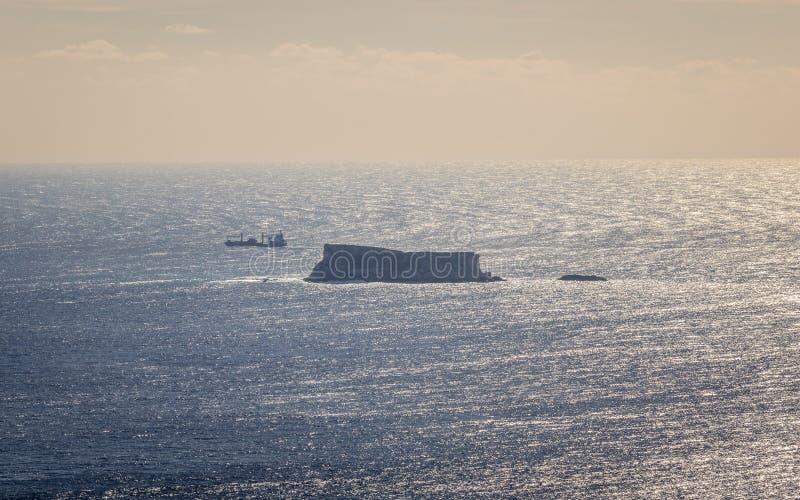 Opinión panorámica sobre la isla maltesa Filfla con una nave del transporte en el cercano Mar claro en el horizonte foto de archivo libre de regalías
