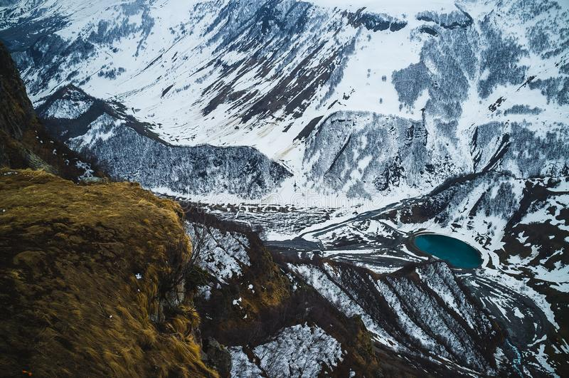 Opinión panorámica sobre las montañas de Kazbek y el valle de la nieve con un lago azul en Georgia imágenes de archivo libres de regalías
