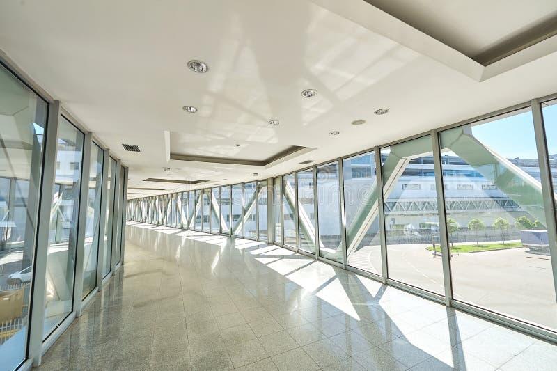 Opinión panorámica sobre pasillo vacío de la oficina con las ventanas de la pared de cristal hecho del metal y del vidrio Constru imagen de archivo libre de regalías