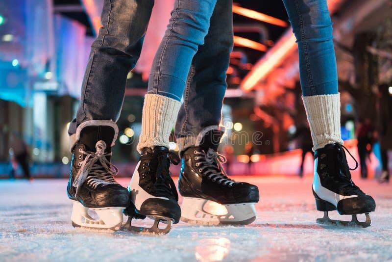 opinión parcial del primer de pares jovenes en el patinaje de hielo de los patines imagen de archivo libre de regalías
