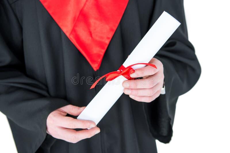 Opinión parcial del primer el hombre joven en el vestido de la graduación que sostiene el diploma fotografía de archivo libre de regalías