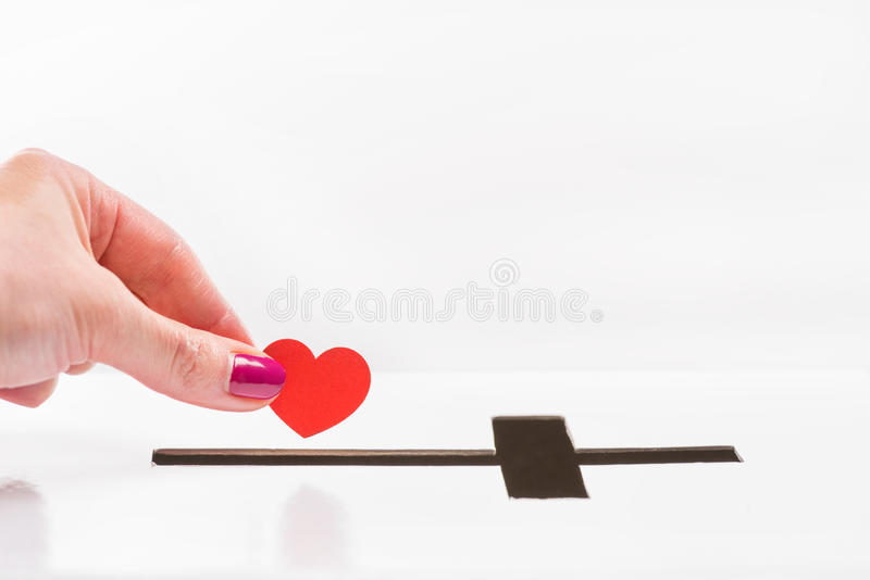 Opinión parcial del primer la mujer que inserta símbolo rojo del corazón en el agujero para las donaciones en la forma de cruz fotografía de archivo