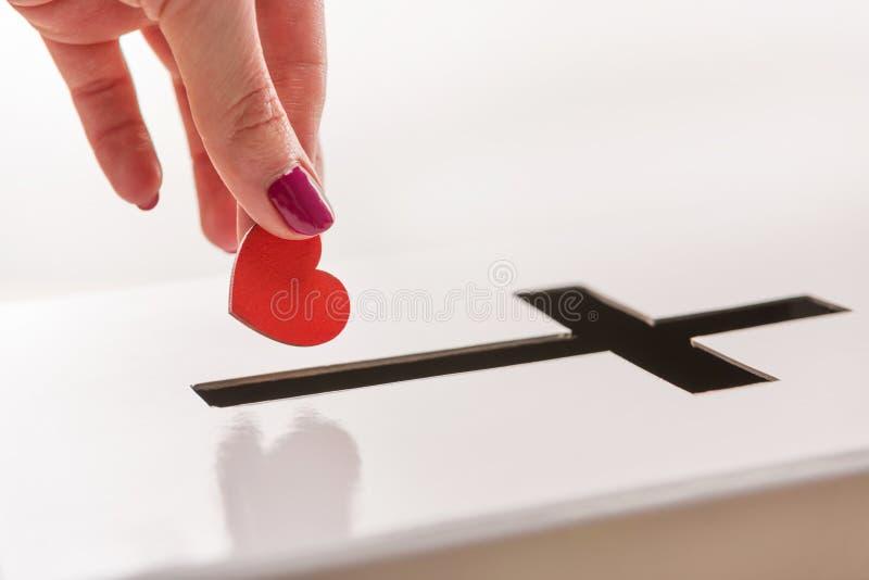 Opinión parcial del primer la mujer que inserta símbolo rojo del corazón en el agujero para las donaciones en la forma de cruz imagen de archivo