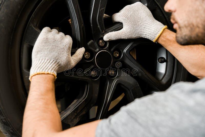 opinión parcial el mecánico de automóviles en guantes protectores que comprueba la rueda del automóvil fotografía de archivo