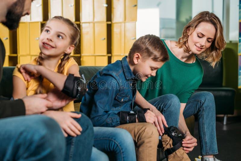 opinión parcial los padres que ayudan a niños a llevar la protección antes de patinar imagenes de archivo