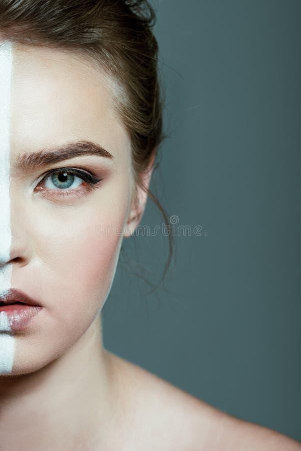 opinión partida en dos la muchacha adolescente hermosa con la línea blanca creativa del arte de cuerpo en cara, imagenes de archivo