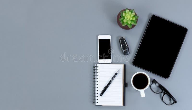 Opinión plana de la endecha del escritorio gris con el techn inalámbrico moderno funcional imagenes de archivo
