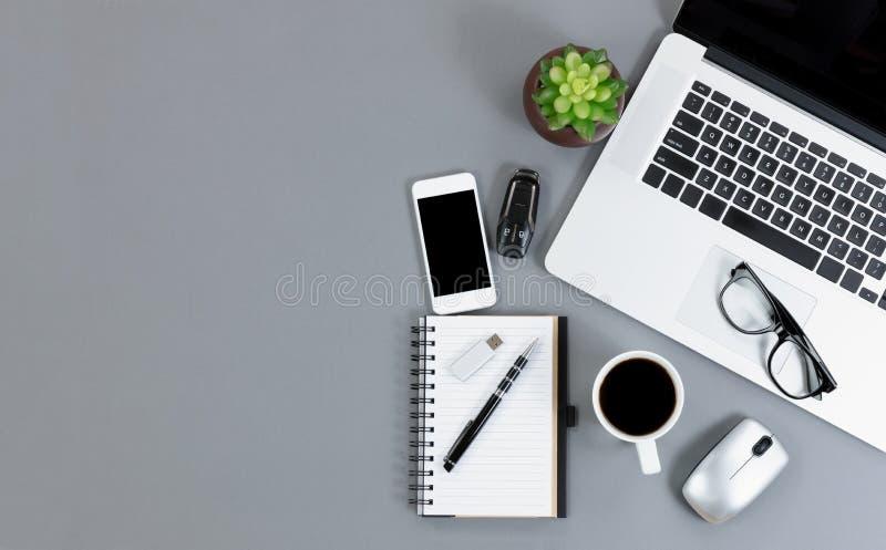 Opinión plana de la endecha del escritorio gris con la tecnología inalámbrica funcional a imagen de archivo